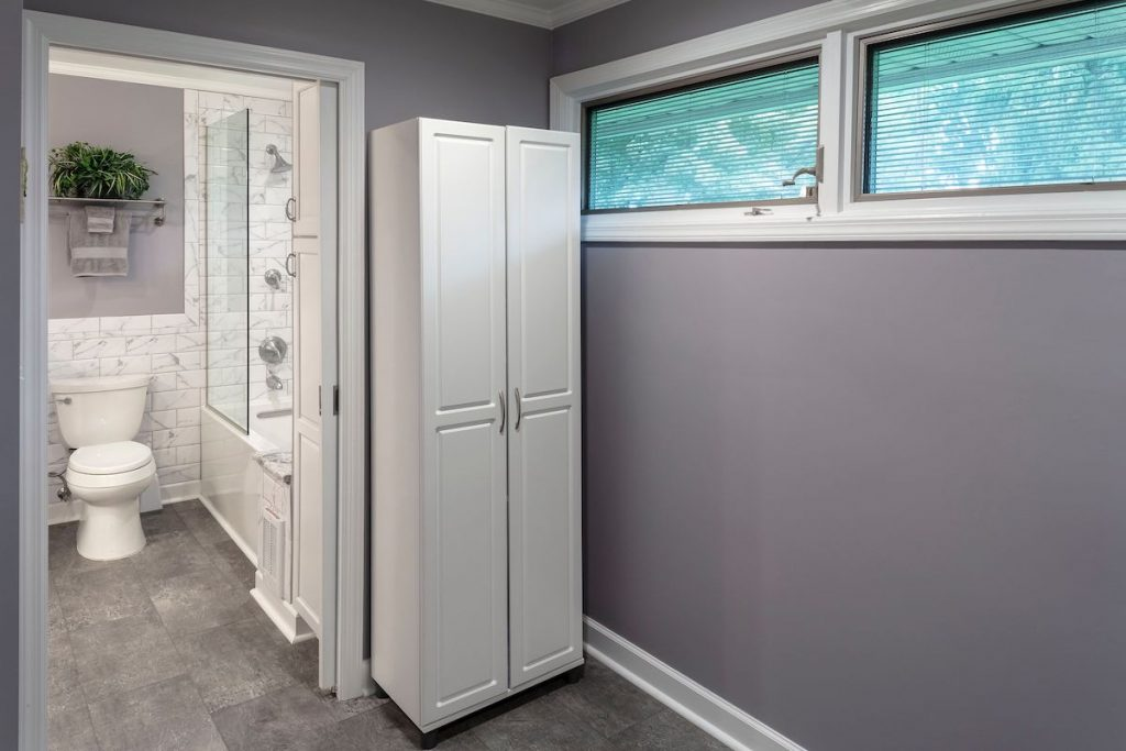 gray bathroom flooring and view of bath from laundry area