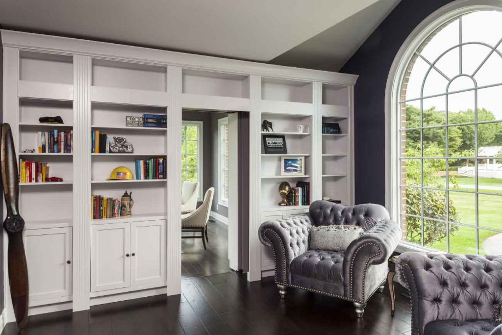 Wall of storage shelves with a hidden door to a home office