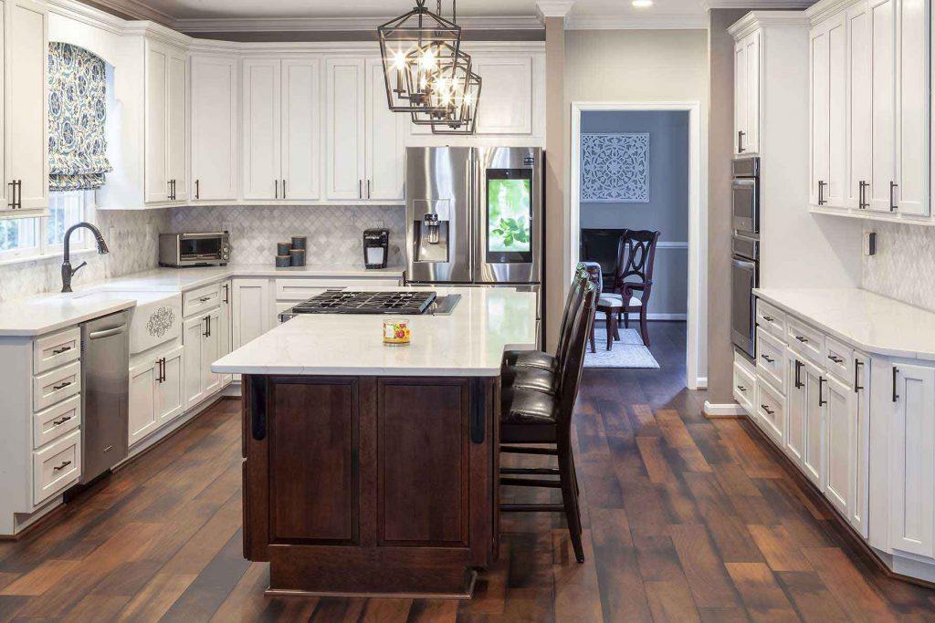 Beautifully remodeled kitchen with dark hardwood flooring, white cabinets, and amazing pendant lights