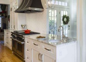 Part of an open-kitchen renovation with a separate sink and unique range hood.