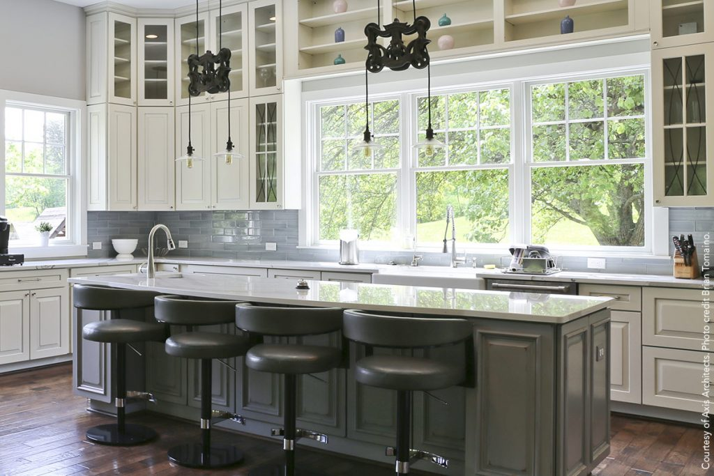 Amazing new kitchen with dark and light-colored cabinets as well as unique pulley-style pendant lights over kitchen island.